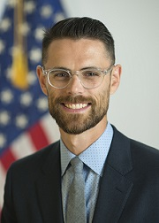 Dr. Ostrovsky wearing a blue collared shirt, grey tie and dark jacket in front of an American flag