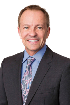 Dr. Bradley Monk wearing a blue collared shirt, grey suit jacket and a paisley tie
