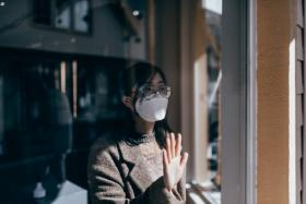 Woman wearing a mask looking out the window