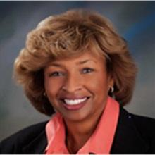 Dr. Rhonda Robinson Beale wearing a black jacket and peach blouse